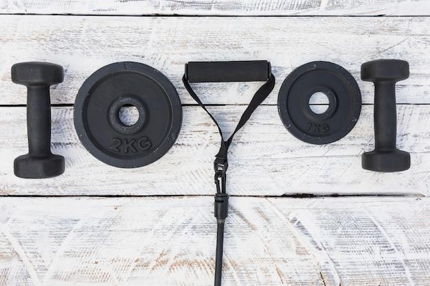 Halteres; placas de peso e cinta de aptidão em plano de fundo texturizado de madeira branco
