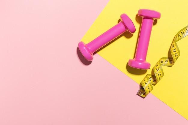 Halteres plana leigos sobre fundo rosa e amarelo