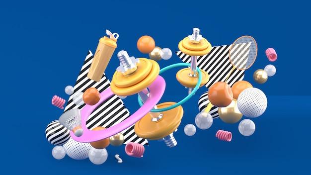 Halteres, raquetes de badminton, garrafas de água e um bambolê entre bolas coloridas em azul. renderização em 3d.