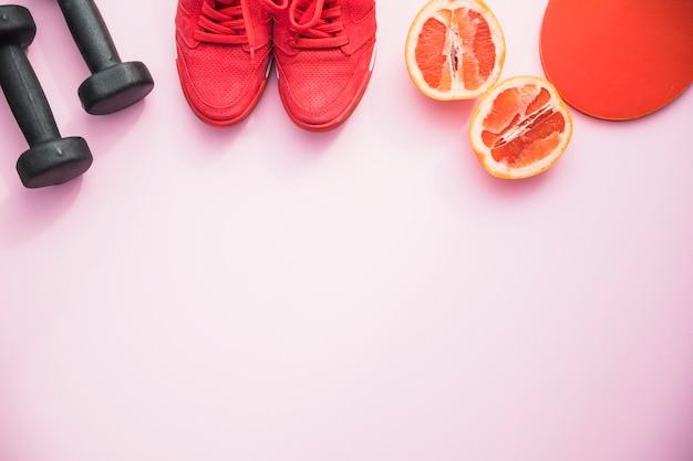 Halteres; sapatos; fruta laranja e ping pong raquete no fundo rosa
