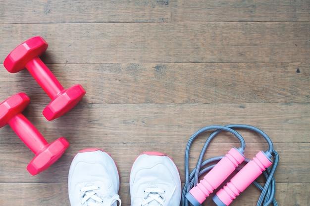 Halteres vermelhos, cordas de salto e sapatos esportivos em fundo de madeira com espaço de cópia, conceito de estilo de vida saudável