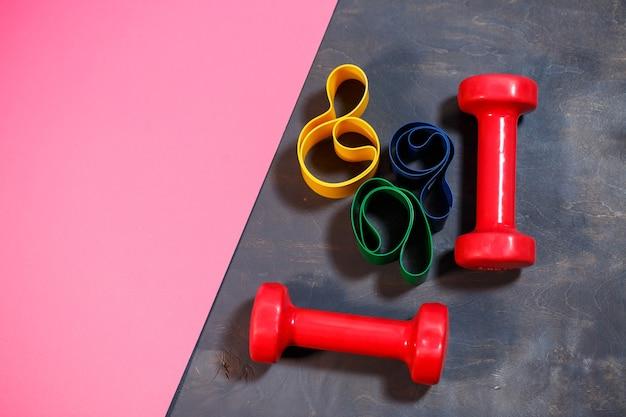Halteres vermelhos e elásticos para esportes em um fundo rosa. estilo de vida saudável. equipamentos de ginástica para musculação. desenvolvimento muscular e treinamento físico