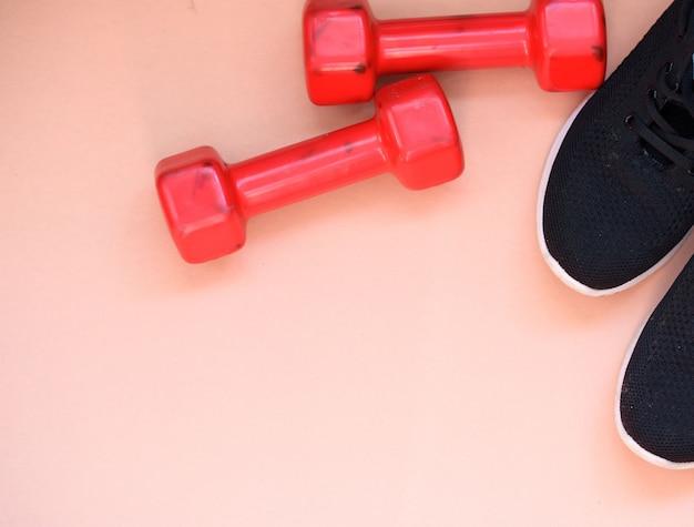 Halteres vermelhos e tênis esportivos pretos sobre um fundo claro
