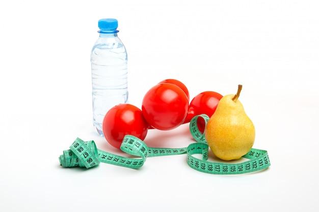 Halteres vermelhos, pêra fresca, fita métrica ou fita métrica e uma garrafa natural de água com gás em um espaço em branco. conceito de estilo de vida saudável, fitness, dieta