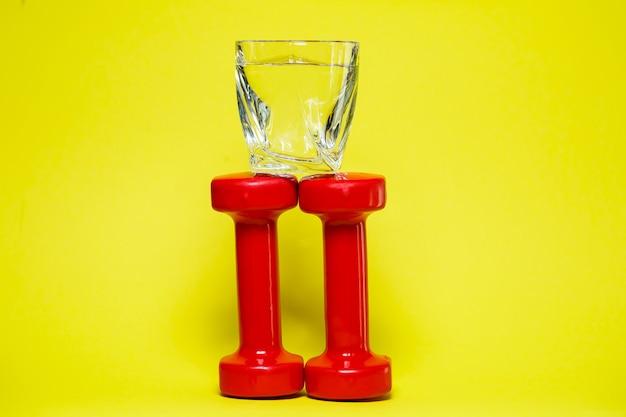 Halteres vermelhos, um copo d'água, fundo colorido, esportes, bebida energética, equipamento para academia