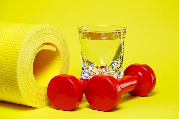 Halteres vermelhos, um copo d'água, um tapete amarelo, fundo colorido, esportes, bebida energética, equipamento para academia