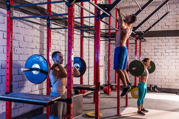 Halterofilismo de grupo de levantamento de peso de barra no ginásio