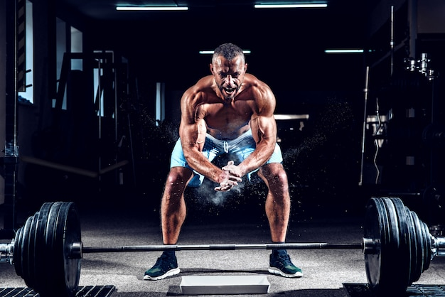 Halterofilista muscular batendo palmas de mãos e se preparando para o treino em uma academia