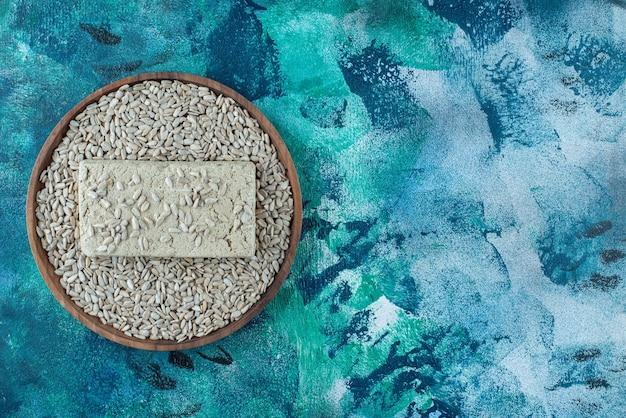 Halva de girassol doce com sementes na placa de madeira, na mesa azul.