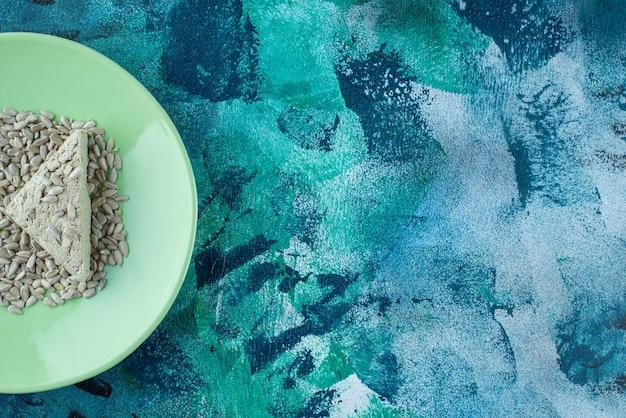 Halva de girassol fatiada com sementes no prato, na mesa de mármore.