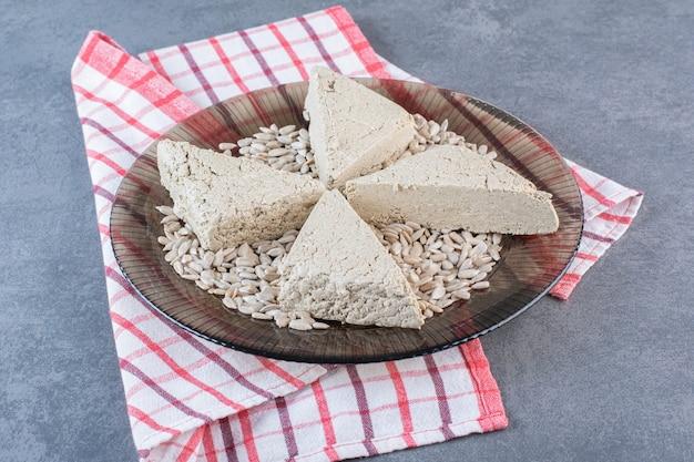 Halva de girassol fatiado com sementes descascadas no prato de vidro sobre um pano de prato, na superfície de mármore