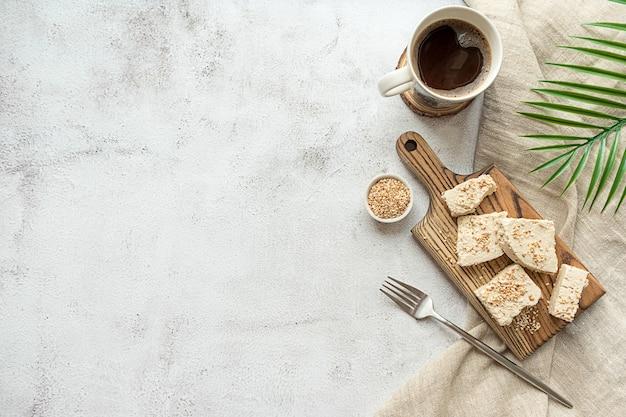 Halva de tahini fatiado em uma placa de madeira plana Foto Premium