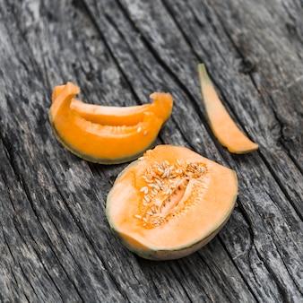 Halved cantaloupe em uma velha mesa de madeira