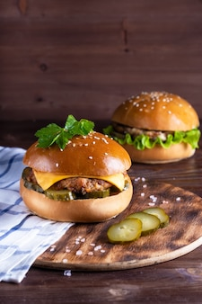 Hamburger caseiro com carne e pepinos na madeira