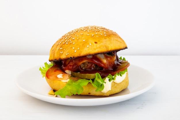 Hamburger saboroso quente em uma placa em um fundo branco. hambúrguer caseiro recheado com rissóis de carne, tomate, pepino em conserva e cebola, maionese, ketchup, queijo e salada. comida rápida