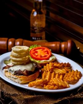 Hambúrguer aberto com carne, molho de queijo, rodelas de cebola e tomate com batatas fritas num prato sobre uma mesa de madeira
