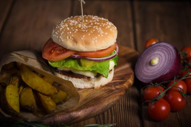 Hambúrguer apetitoso com carne, batata e queijo em uma superfície de madeira