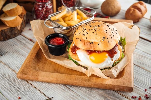 Hambúrguer apetitoso com ovo frito na placa de madeira