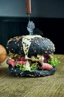 Hambúrguer apetitoso com pães pretos, molho branco, carne assada e alface, guarnecido com batatas fritas em uma superfície de madeira, close-up, foco seletivo