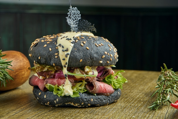 Hambúrguer apetitoso com pães pretos, molho branco, rosbife e alface, guarnecido com batatas fritas numa superfície de madeira, close-up
