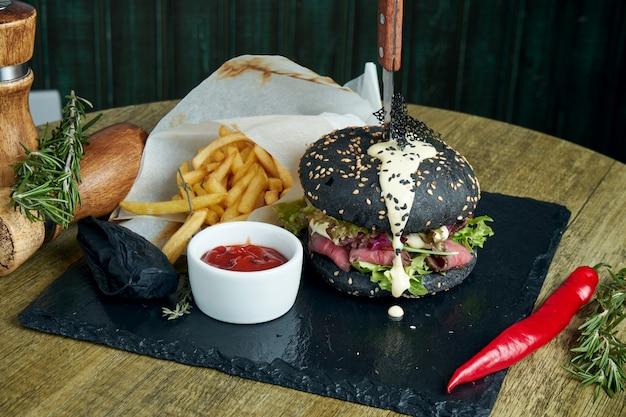 Hambúrguer apetitoso com pão preto, molho branco, rosbife e alface, guarnecido com batatas fritas em uma bandeja de ardósia preta. feche acima da vista.