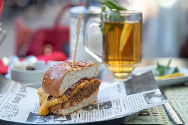 Hambúrguer apetitoso e um copo de chá com limão em um café de rua
