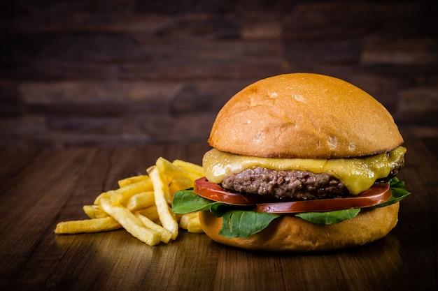Hambúrguer artesanal com queijo, folhas de foguete e batatas fritas na mesa de madeira