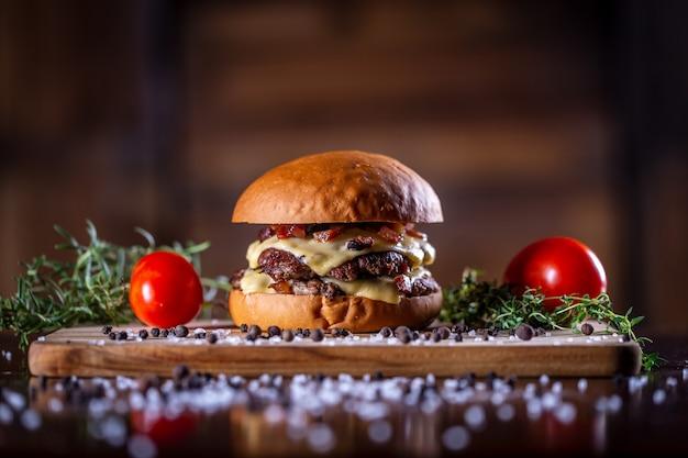 Hambúrguer artesanal de carne esmagada com queijo, bacon e molho em fundo de madeira