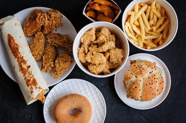 Hambúrguer, batatas fritas, donut, nuggets e chocolate em preto