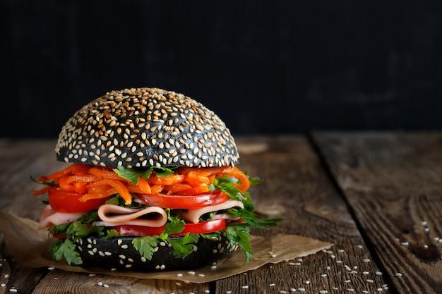 Hambúrguer brilhante apetitoso fresco com sementes de gergelim com legumes frescos (tomate, pimentão)