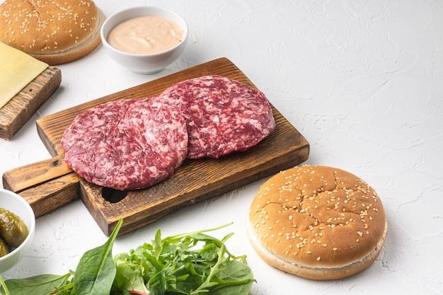 Hambúrguer caseiro. bolinhos de carne crua, pãezinhos de gergelim com outros ingredientes servidos, em uma mesa de pedra branca