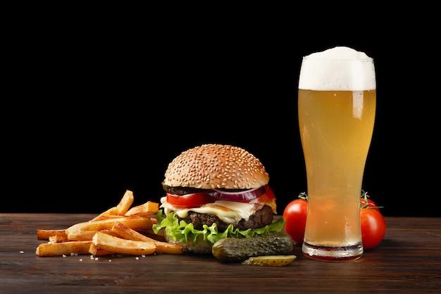 Hambúrguer caseiro com batatas fritas e copo de cerveja na mesa de madeira. fastfood em fundo escuro