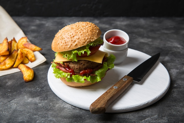 Hambúrguer caseiro com batatas grelhadas, servido com molho de ketchup. hambúrguer com costeleta de carne.