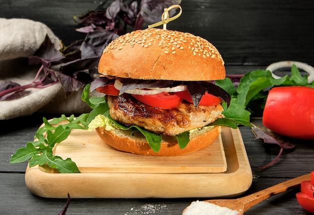 Hambúrguer caseiro com bife de porco frito, tomate vermelho