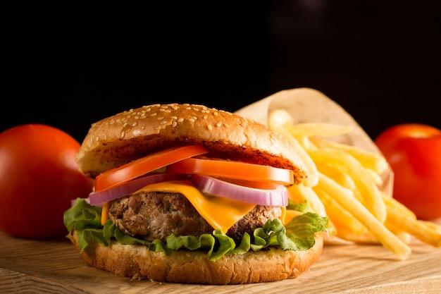 Hambúrguer caseiro com carne, cebola, tomate, alface e queijo. hambúrguer fresco fechar na mesa rústica de madeira com batata frita, cerveja e batatas fritas. hamburguer de queijo.