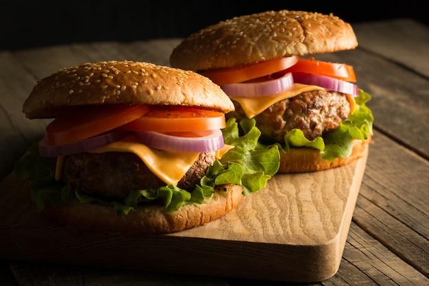 Hambúrguer caseiro com carne, cebola, tomate, alface e queijo. hambúrguer fresco fechar na mesa rústica de madeira com batata frita, cerveja e batatas fritas. x-burguer.