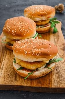 Hambúrguer caseiro com costeleta de frango em uma longa tábua de madeira