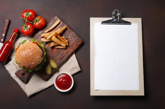 Hambúrguer caseiro com ingredientes carne, tomate, alface, queijo, cebola, pepino e batata frita na tábua e fundo enferrujado