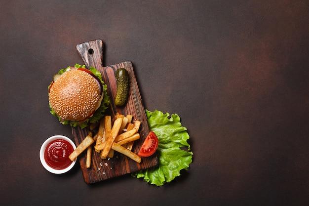 Hambúrguer caseiro com ingredientes carne, tomate, alface, queijo, cebola, pepino e batata frita na tábua