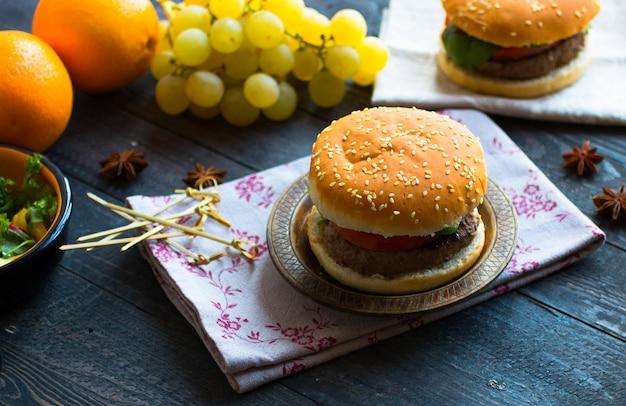 Hambúrguer caseiro com legumes, especiarias e carne de bovino em um de madeira