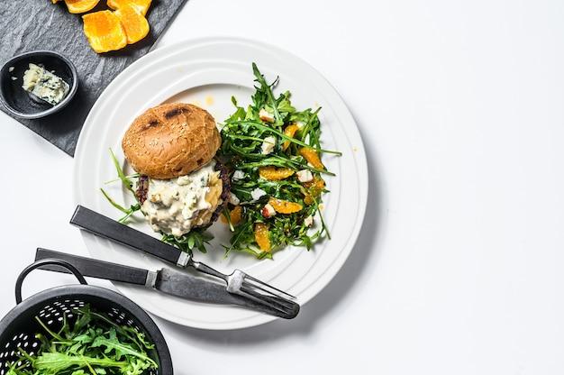 Hambúrguer caseiro com queijo azul, marmelada de carne e cebola marmoreada, um prato de salada com rúcula e laranjas. fundo branco. vista do topo. copie o espaço
