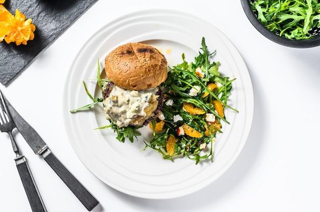 Hambúrguer caseiro com queijo azul, marmelada de carne e cebola marmoreada, um prato de salada com rúcula e laranjas. fundo branco. vista do topo