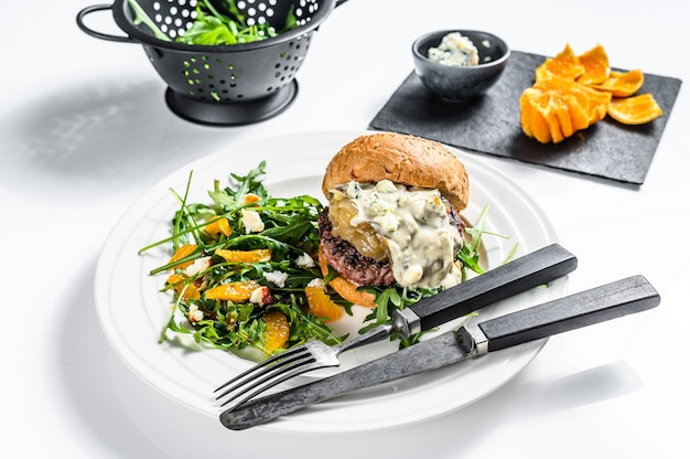 Hambúrguer caseiro com queijo azul, marmelada de carne e cebola marmoreada, um prato de salada com rúcula e laranjas. superfície branca. vista do topo