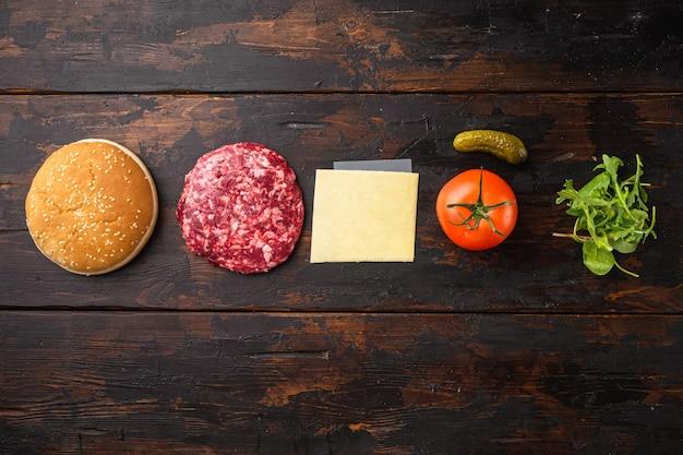 Hambúrguer caseiro. conjunto de rissóis de carne crua, pãezinhos de gergelim com outros ingredientes, em uma velha mesa de madeira