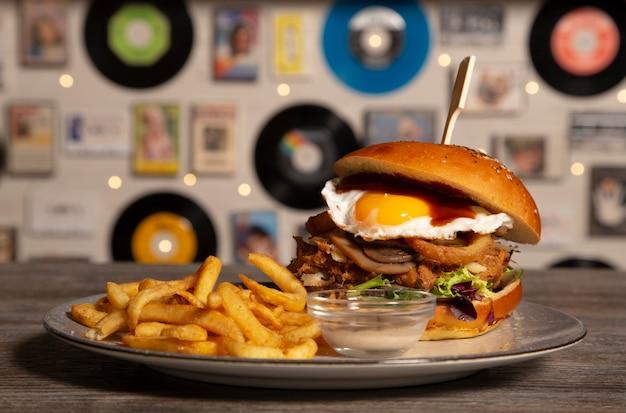 Hambúrguer caseiro de carne de porco com molho de churrasco de ovo frito com batatas fritas na mesa de madeira. imagem isolada