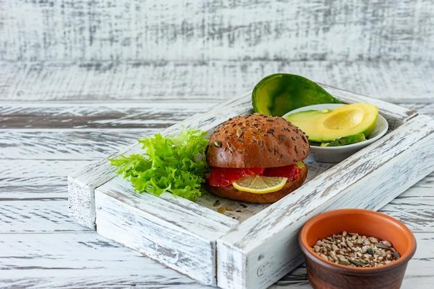 Hambúrguer caseiro de salmão orgânico com tomate, salada de milho e avogado em fundo de madeira. alimentos orgânicos saudáveis.