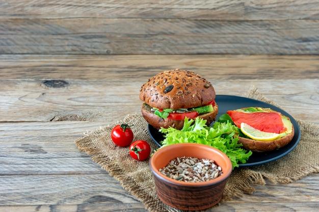 Hambúrguer caseiro de salmão orgânico com tomate, salada de milho e avogado em um prato no fundo de madeira. alimentos orgânicos saudáveis.