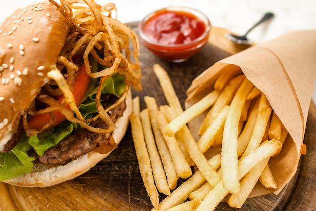 Hambúrguer caseiro fresco com batata frita em papel de padaria, servido com molho de ketchup