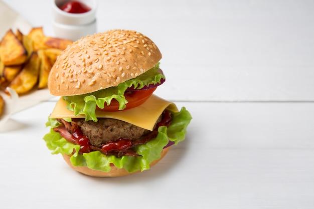 Hambúrguer caseiro fresco com carne, ketchup e batatas fritas, sobre um fundo claro de madeira. copie o espaço.