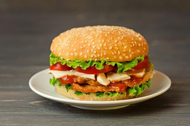 Hambúrguer caseiro na mesa de madeira rústica. delicioso hambúrguer grelhado.